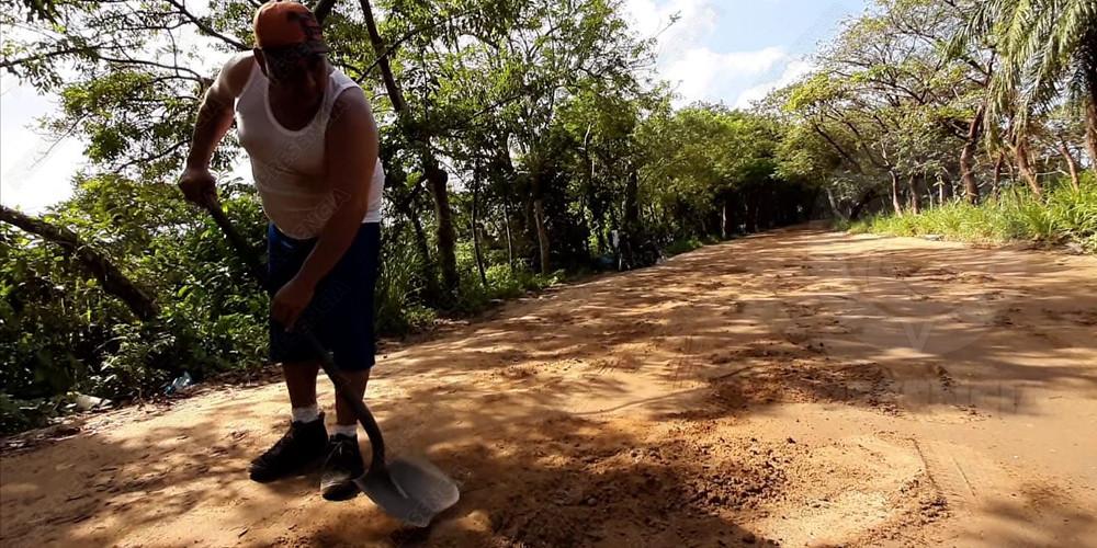 Vicente se gana la vida tapando baches en carretera