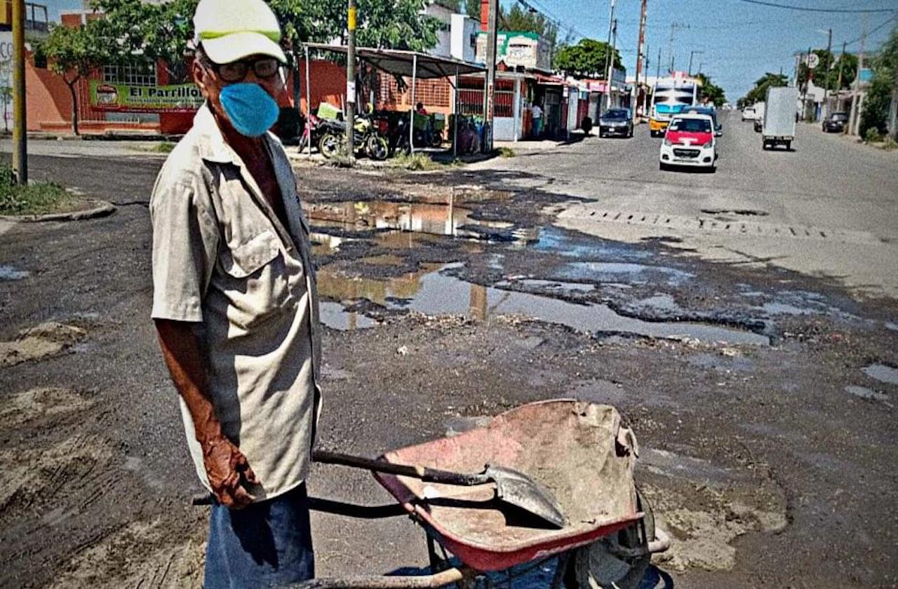Clemente rellena baches para mantenerse en la pandemia