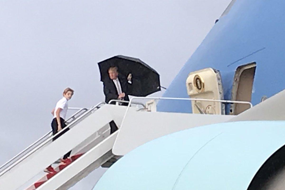 Trump se cubre de la lluvia dejando a su esposa e hijo atrás