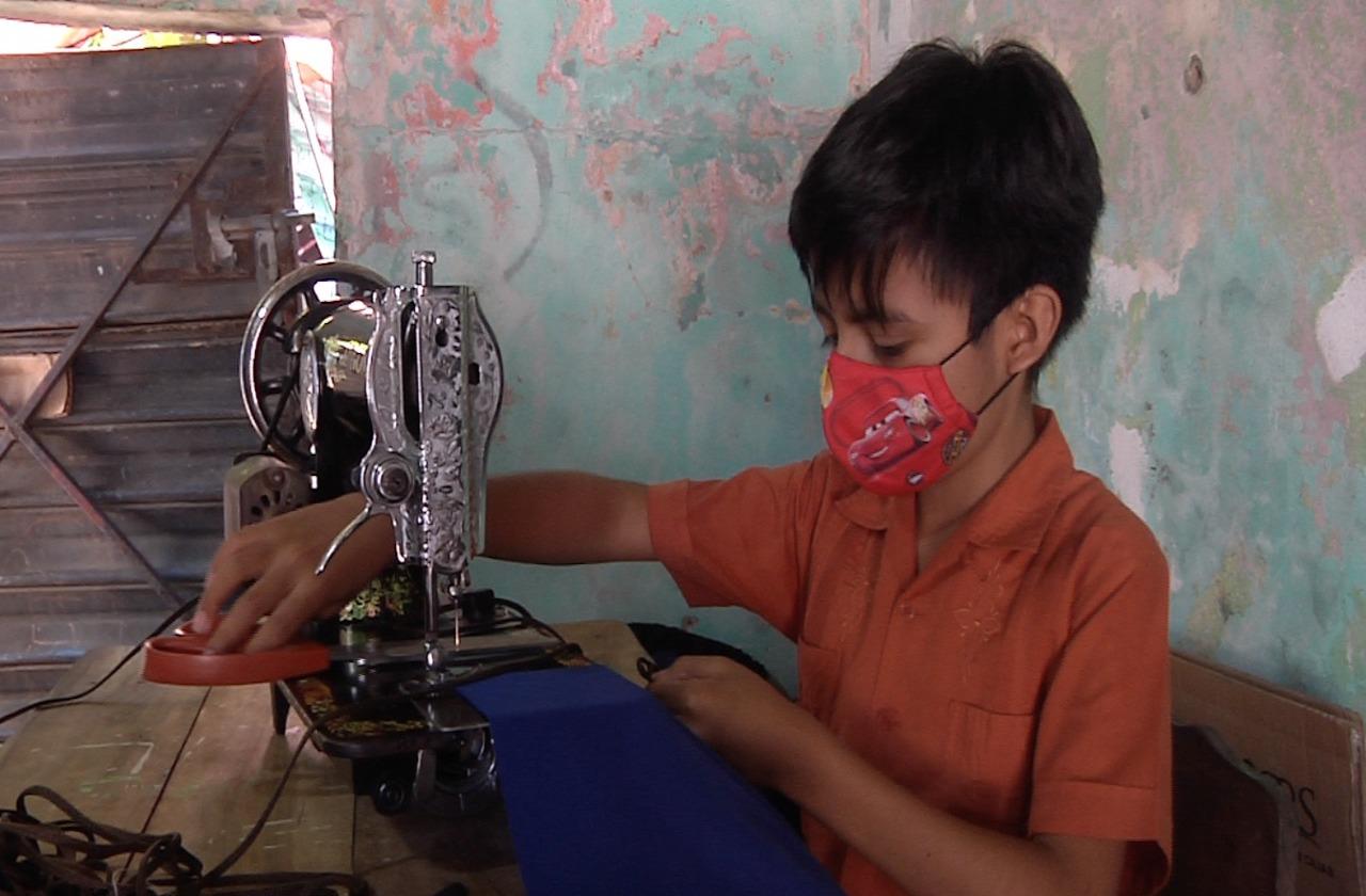 Eliazar de 10 años, confecciona mochilas para ayudar a su familia