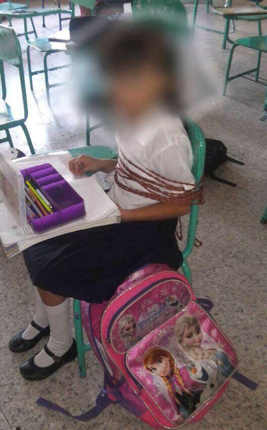 Maestra amarra niña con un mecate en primaria de Veracruz