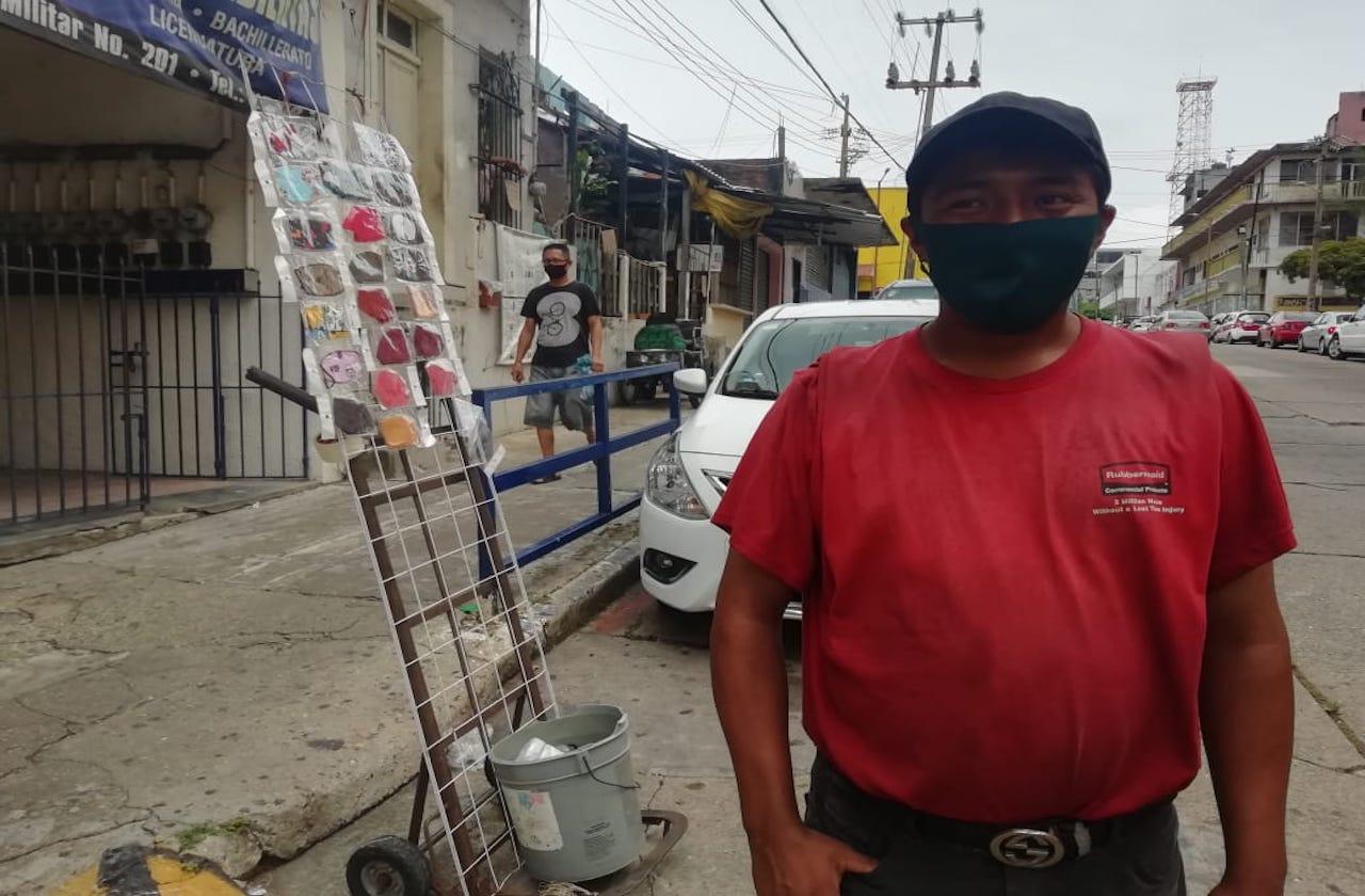 Mientras acomoda vehículos, Miguel vende cubrebocas