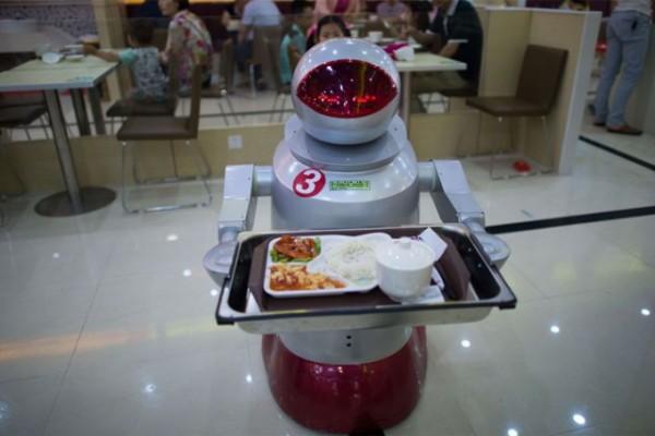 Robots sirven comida que androides cocinan en un restaurante